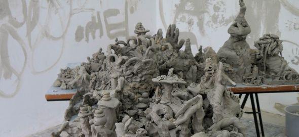 Hunderte verspielter Formen und plastischer Skulpturen aus Ton, die alle dicht gedrängt vor und auf einem Ateliertisch stehen.