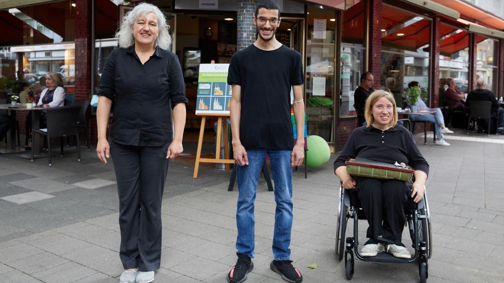 Die Mitarbeiter*innen stehen vor dem Café und lächeln in die Kamera. Die Mitarbeiterin  auf der rechten Seite sitzt im Rollstuhl.