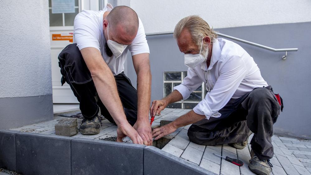 Zwei Bauarbeiter setzen die letzten Steine in eine frisch gebaute Rampe ein. Beide tragen einen Mund-Nasen-Schutz.