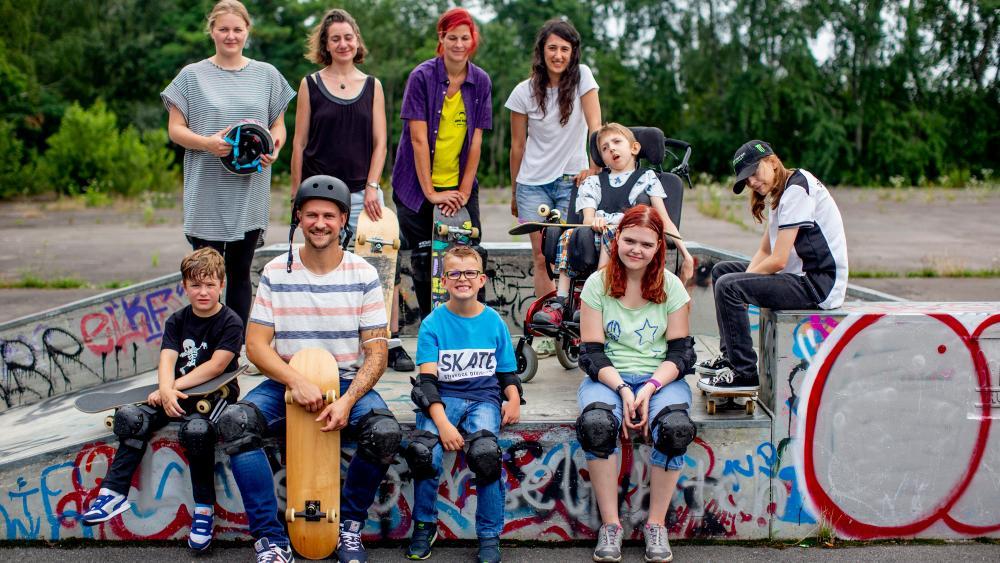Eine Gruppe Kinder und Jugendliche, sowie ein Mann, sitzen auf einer Skateboard-Rampe. Eine JUnge sitzt im Rollstuhl.