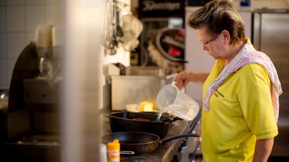 Eine Frau giesst Wasser eine Pfanne.