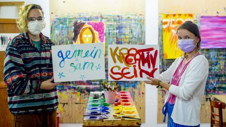 """Zwei Frauen stehen in einem Atelier und halten jeweils ein Schild hoch. Auf dem einen steht """"gemeinsam"""", auf dem anderen """"kreativ sein""""."""
