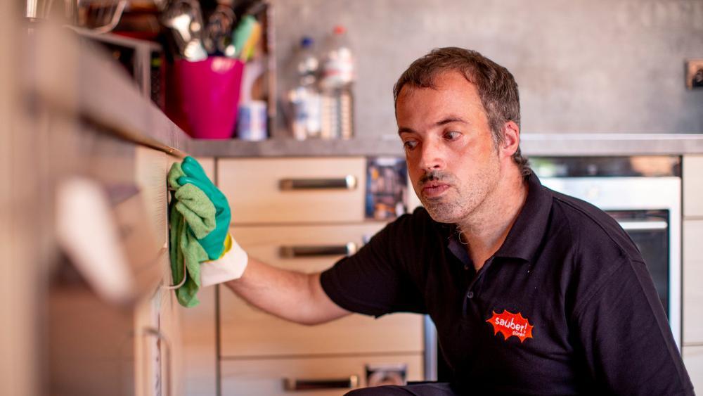 Ein Mann putzt die Front der Küchenschränke.