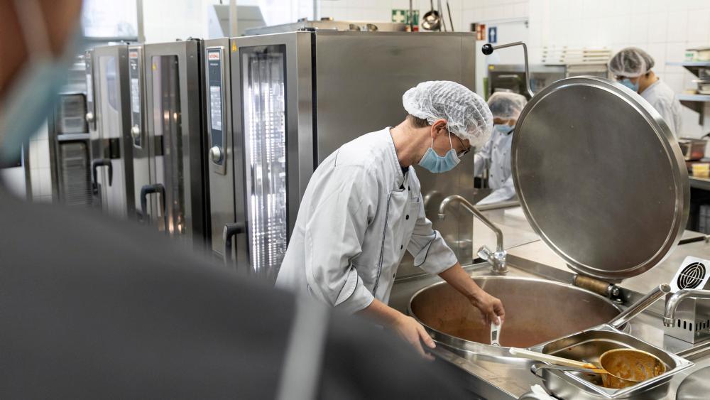 Ein Mitarbeiter misst mit einem Thermometer die Temperartur des Essens in einem großen Kochtopf.