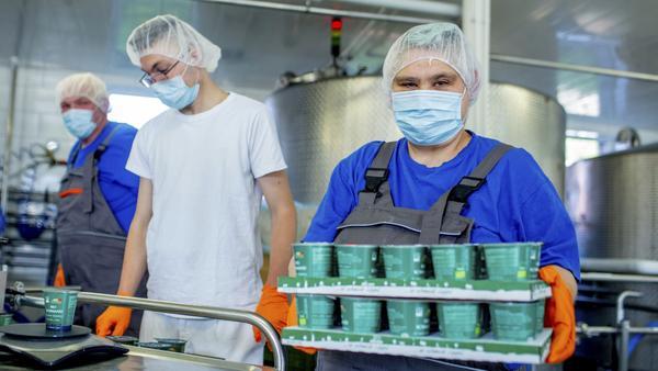 Ein Molkerei-Mitarbeiter trägt eine Palette mit Joghurtbechern.