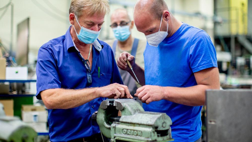 An einem Schraubstock bearbeiten zwei Mitarbeiter ein Stück Metall.