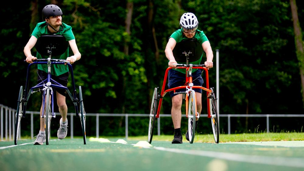 Zwei junge Männer trainieren auf der Laufbahn mit ihren Rädern.