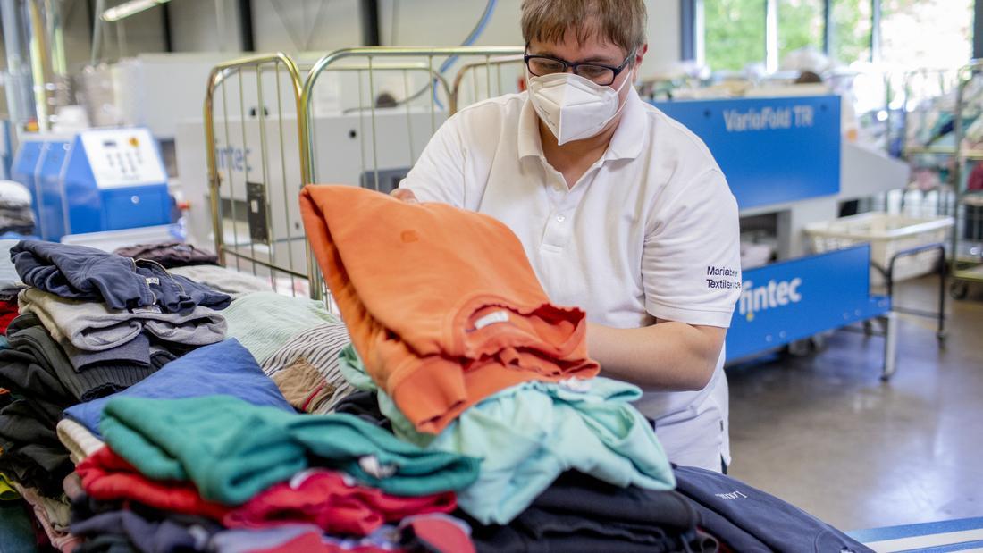 Eine Mitarbeiter*in legt Wäsche aufeinander.