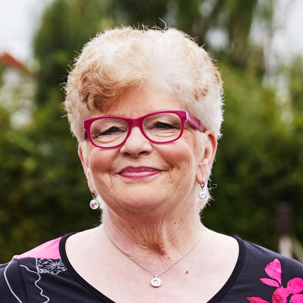 Eine ältere Frau mit kurzem, hellem Haar und pinker Brille lächelt in die Kamera.