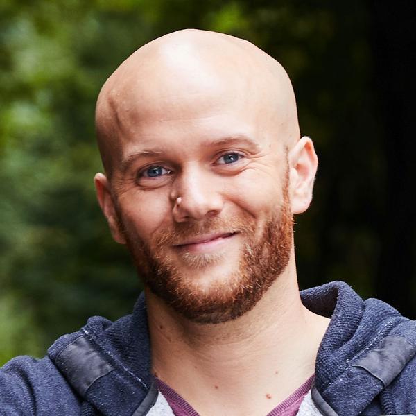 Ein Mann mit Glatze, Vollbart und Kapuzenpulli hält lächelnd ein Glücks-Los in die Kamera.