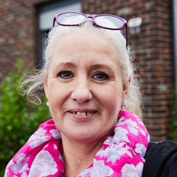 Eine Frau mit blondem Pferdeschwanz und pinkem Halstuch lächelt in die Kamera. Sie steht vor ihrem Haus.