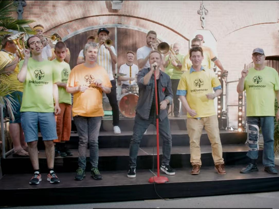 Sänger*innen mit und ohne Behinderung stehen gemeinsam mit einer Brass-Band auf der Bühne und singen.