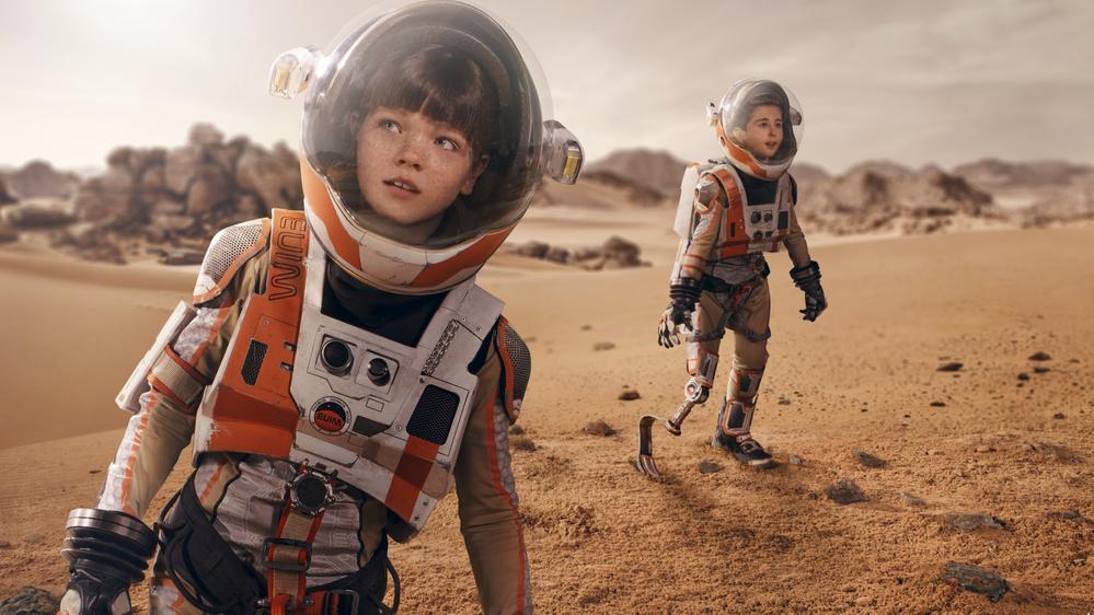 Zwei Kinder in Raumanzügen laufen über die Oberfläche des Mars. Eines der Kinder hat eine Beinprothese.