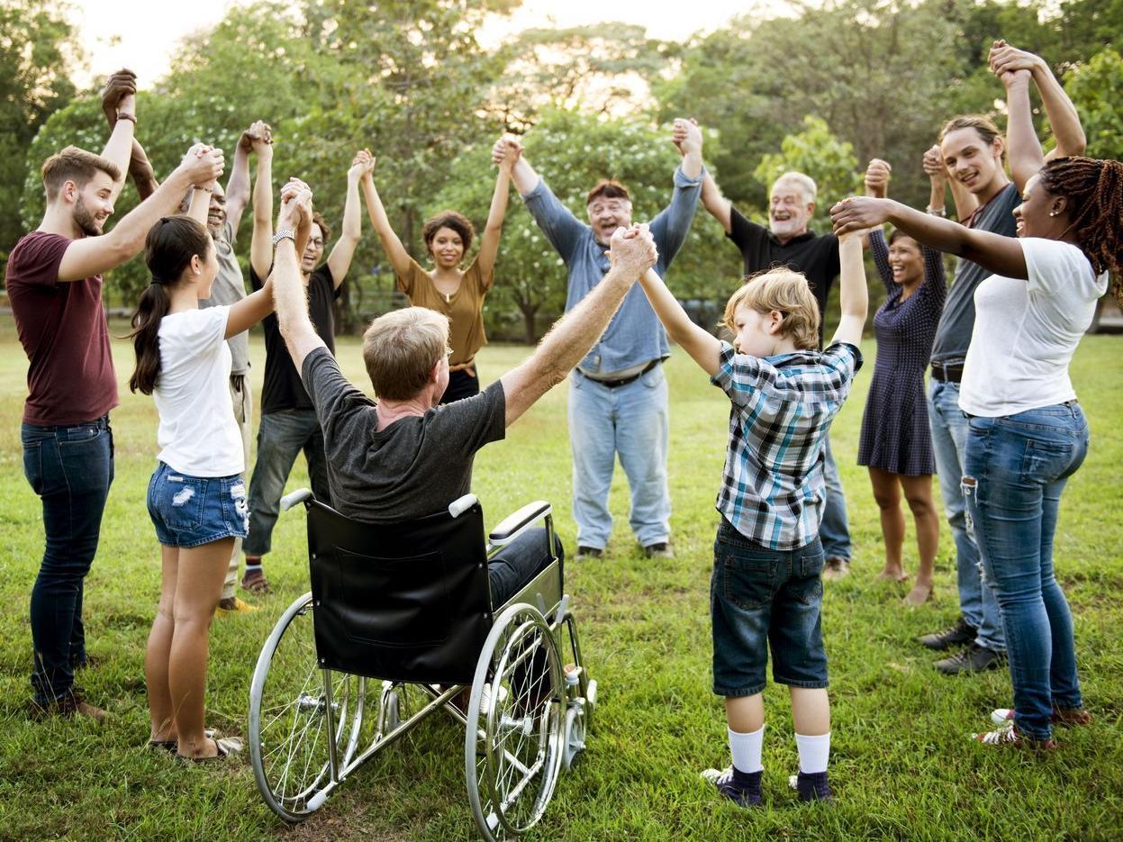 Eine Gruppe von Menschen mit und ohne Behinderung, unterschiedlichen Alters und Herkunft halten sich an den Händen und bilden einen Kreis.