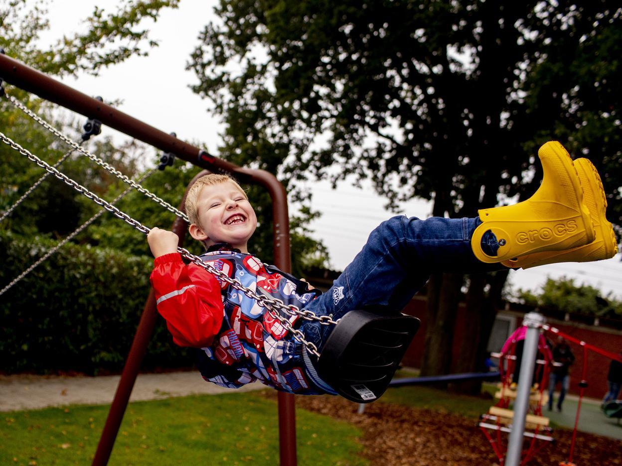 Ein Junge in gelben Gummistiefeln sitzt lachend auf einer Schaukel.