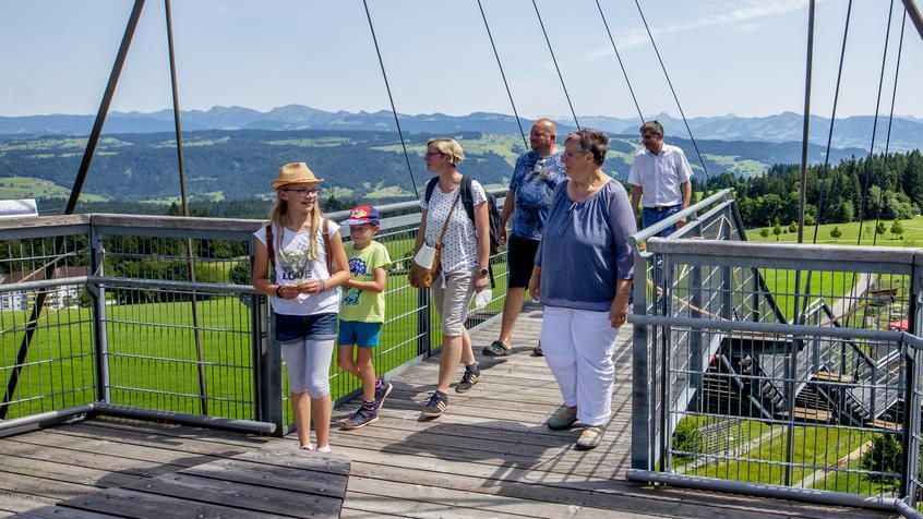 Eine Gruppe von Menschen steigt die Treppe zum Skywalk hinauf. Im Hintergrund sind die Alpen zu sehen.