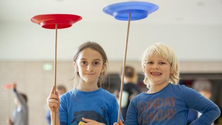 Zwei Kinder halten Jonglier-Teller und lachen in die Kamera.