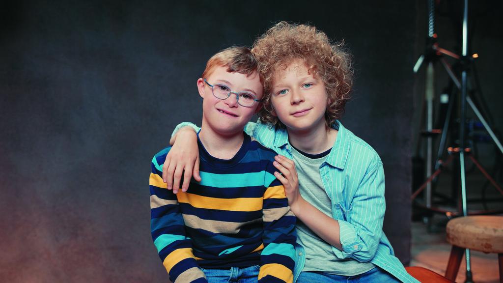 Zwei Jungen sitzen in einem Studio nebeneinander auf einer Bank. Der eine Junge legt den Arm um seinen Freund.