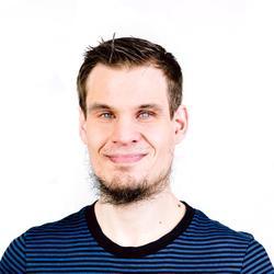 Ein junger Mann mit braunen Haaren und Bart schaut in die Kamera. Er trägt ein schwarz blau gestreiftes T-Shirt.